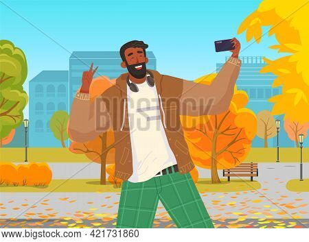 Young Guy Doing Live Streaming In Autumn Park. Video Blogging Concept. Social Media Network Blogger.