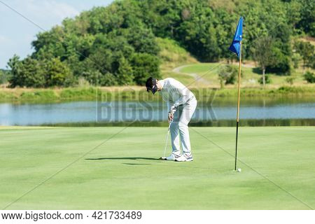 Golfer Man Playing Golf Aiming Shot For Putting Ball On The Hole With Club On Green Course.  Profess