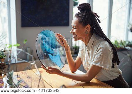 Happy Female Artist Admiring Her Abstract Artwork