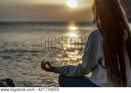 Beautiful Woman With Long Flowing Hair Practices Yoga On The Beach, Yoga Ardha Padmasana In The Half