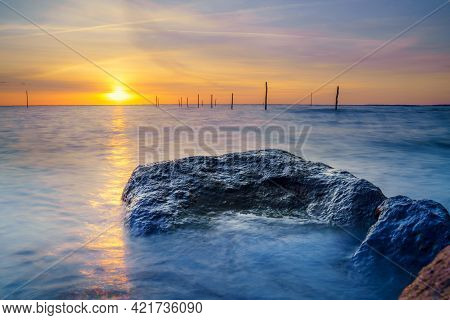Setting Sun Above Dutch Ijsselmeer With Boulders In Foreground, Lake Ijssel, Flevoland, Netherlands