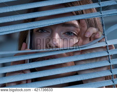 The woman with  the phone peeping out the window