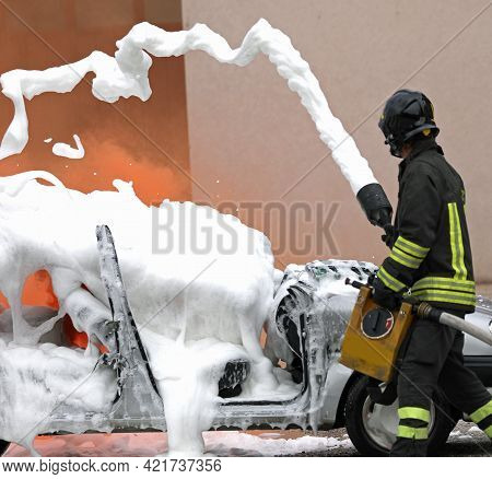 Fire Brigade Team In Action While Extinguishing The Fire After The Car Accident