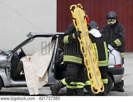 Firefighters With The Stretcher To Help The Injured Person After A Disastrous Car Accident And The D