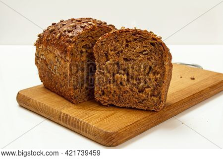 Cut Loaf Of Rye Bread On A Wooden Cutting Board With The White Background.