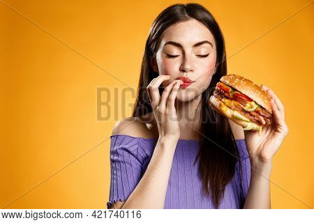 Woman Eating Cheeseburger With Satisfaction. Girl Enjoys Tasty Hamburger Takeaway, Licking Fingers D