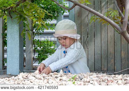 Baby Girl Collecting Stones In Garden. Outdoor Creative Activities For Kids