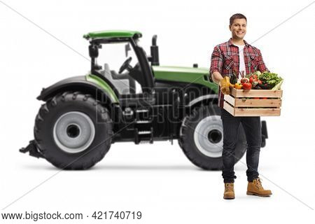 Farmer with a crate full of vegetables standing in front of a tractor isolated on white background