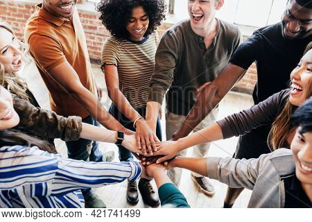 Group of diverse people stacking hands in the middle