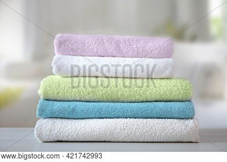 Colorful Terry Towels Stack On Table Indoors. Bathroom Shower Items. Household. Domestic Linen.