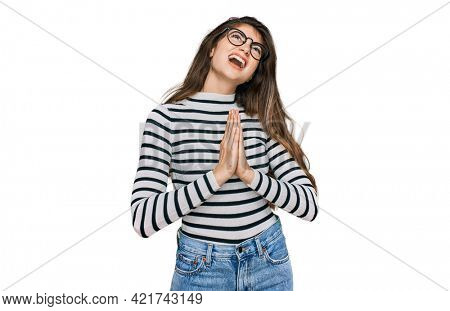 Young beautiful teen girl wearing casual clothes and glasses begging and praying with hands together with hope expression on face very emotional and worried. begging.