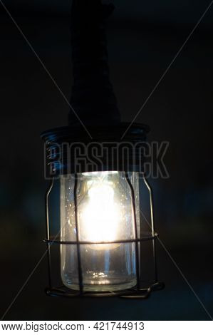 Stylish Retro Electric Light In Protective Metal Grid On Blurred Dark Background. Lamp In Metal Grid