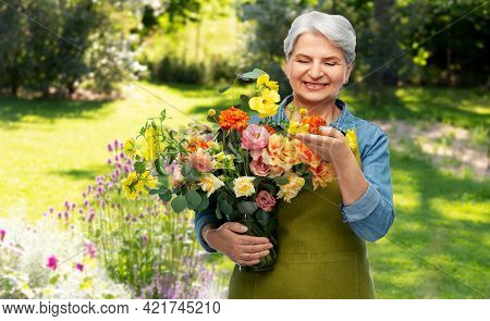 gardening, floristics and old people concept - portrait of smiling senior woman in green apron with bunch of flower over summer garden background
