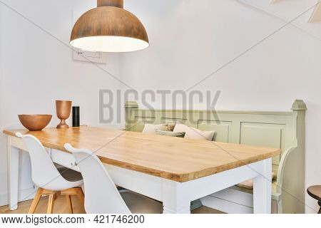Cozy Dining Area With White And Wood Table In Corner And Green Classic Bench Under Pendant Lamp