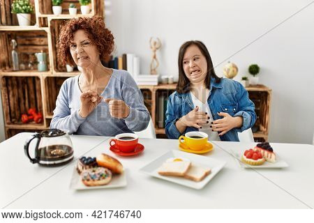 Family of mother and down syndrome daughter sitting at home eating breakfast disgusted expression, displeased and fearful doing disgust face because aversion reaction. with hands raised