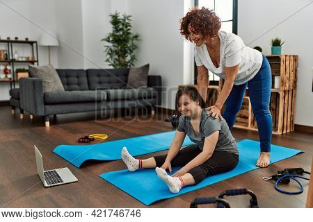 Mature mother and down syndrome daughter doing exercise at home. Stretching at the living room