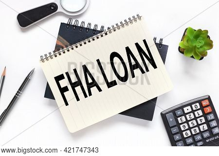 Fha Loan. An Open Notebook Lies On A Closed Notebook Near A Calculator And A Magnifying Glass On A W