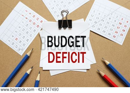 Budget Deficit. The Text On The Sticker Near The Calendar And Karagdash. The Paper Is Clamped With A