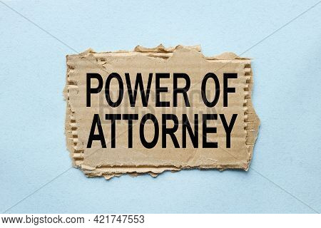 Power Of Attorney. Text On Torn Paper On Blue Background