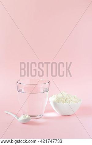 Protein Or Collagen Powder And A Glass Of Water On A Pink Background With A Copy Space. Extra Protei