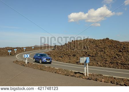 Car Driving On A Road Of Lanzarote Island In Spain