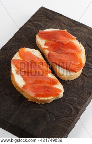 Two open-face sandwiches with smoked salmon on wooden tray