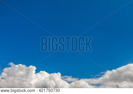 Blue summer sky with cumulus clouds at the bottom - natural background with copy space