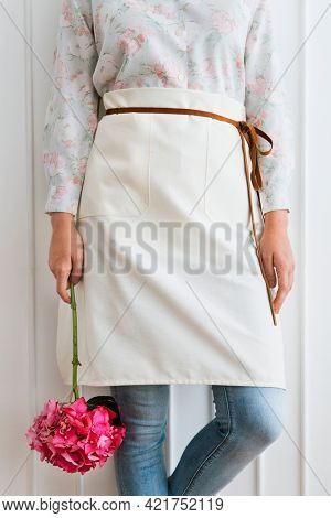 Florist in a white apron  holding a pink hydrangea