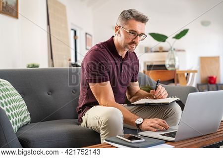 Mature business man writing notes on agenda and working on laptop from home. Casual freelance in smart working on laptop in living room. Serious focused mid adult man sitting on sofa in telecommuting.