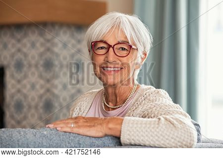 Portrait of beautiful senior woman with white hair and eyeglasses. Happy old woman relaxing on couch at home while looking at camera with big grin. Successful mature woman smiling while wearing specs.