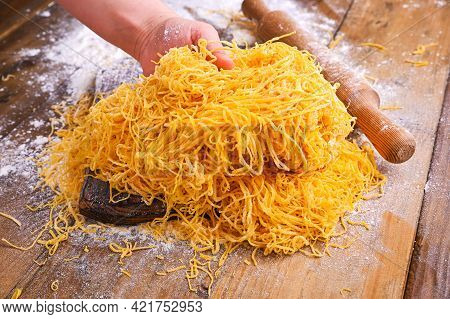 Italian Egg Pasta, Homemade And Fresh On A Wooden Table. Tagliatelle Pasta Is Thin. In Hand Traditio