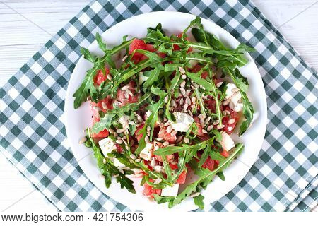 A Portion Of Fresh Salad With Watermelon, Feta Cheese, Leaves Of Arugula And Basil And Peeled Sunflo