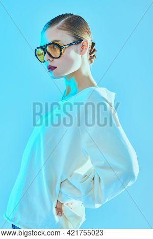 Beautiful stylish girl poses in white sweatshirt and fashionable sunglasses. Women's accessories, glasses.