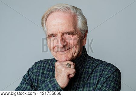 Happy senior man with his hand on his chin