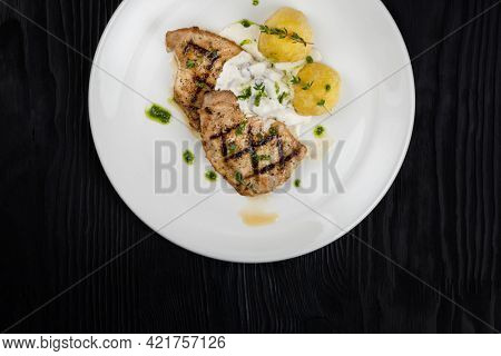 Grilled pork meat with mushroom sauce and potato on white plate on wooden black background