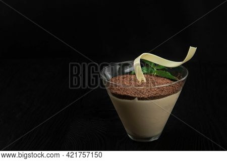 Delicious Italian dessert tiramisu, on a black wooden background decorated with mint leaf, with copy space.