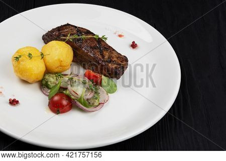 Grilled beef skirt steak meat with potato and vegetables on white plate on wooden black background