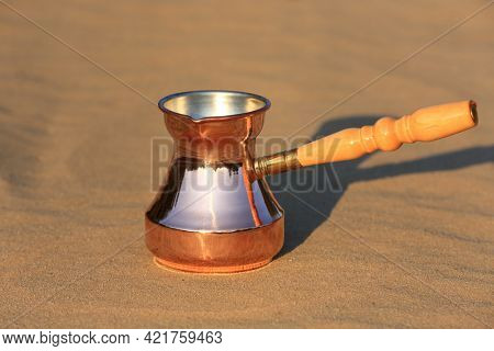 copper coffee turk in the sand surface in desert