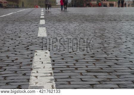 White Markings On The Cobblestone Pavement Made Of Natural Stone On Red Square In Moscow In Russia.