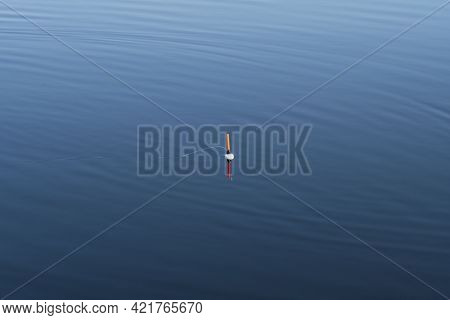 Fishing Float In Blue Water Background. Fishing Concept. Float In The River Water Close-up. Fishing