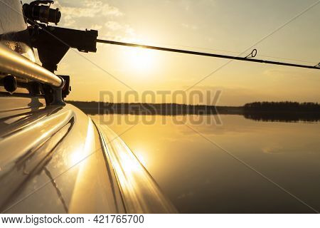 Fishing Rod Spinning With The Line Close-up. Fishing Rod In Rod Holder In Motor Boat Due The Fishery