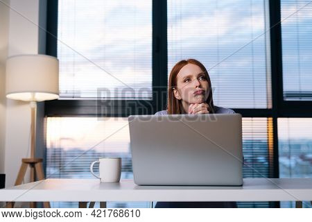 Front View Of Concerned Redhead Woman Working On Laptop Computer Looking Away Thinking Solving Probl