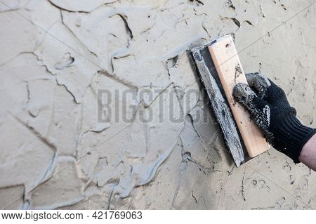 Decorative plaster coating, master makes the texture of venetian plastering on the wall with trowel, no face