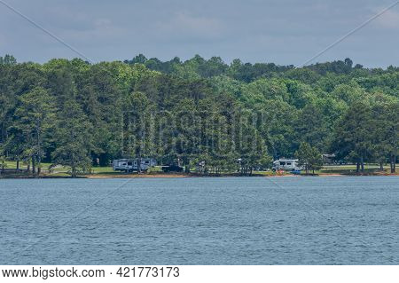 Across The Lake Is A Campground Along The Water With Campers And Tents Picnic Tables And Folding Cha
