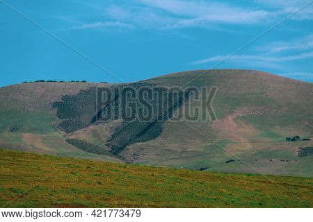 Low Mountain Hillside Lush With Green Grass And Farmland With Bright Sunny Blue Sky
