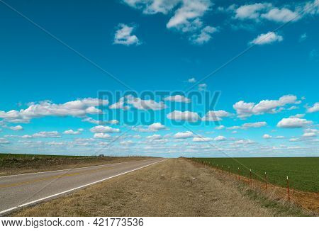 Lonely Single Road Highway With Fields On Sides Leading Into The Horizon And Blue Sky With White Puf
