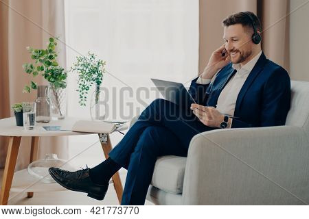 Smiling Business Person In Suit Wearing Headset Having Video Call, Working Online On Laptop While Si