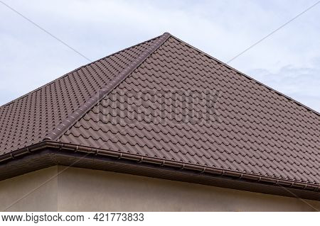 Roof Structure Covered With Brown Metal Tiles On A Bright Sunny Day. Modern Housing Construction. Ty