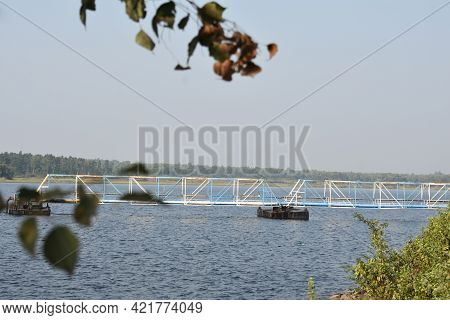 A Beautiful Blue Lake With Green Leaves In The Foreground