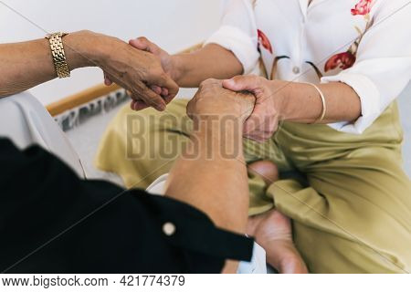 Cropped Shot Of Senior Woman And Adult Daughter Holding Hands While Sitting Together At Home.